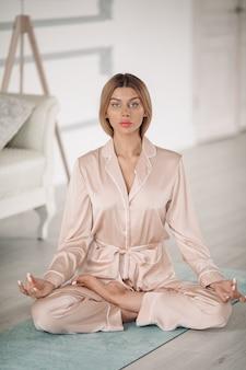 Hübsche junge frau, die yoga-übung macht, während sie auf trainingsmatte sitzt. gesundes lebensstilkonzept. morgenfitness