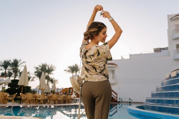 Hübsche junge frau, die zeit in der nähe des schönen pools genießt, spaß im kurhotel, im resort, im urlaub, im urlaub hat und mit den händen nach oben tanzt. trägt ein stilvolles t-shirt und eine graue freizeithose. blick von hinten