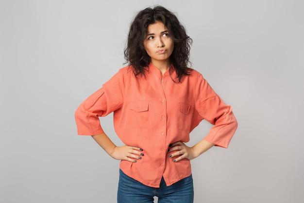 Hübsche junge frau frustriert mit einem problem, denken, verwirrte emotion, isoliert, orange hemd, hipster-stil tragend