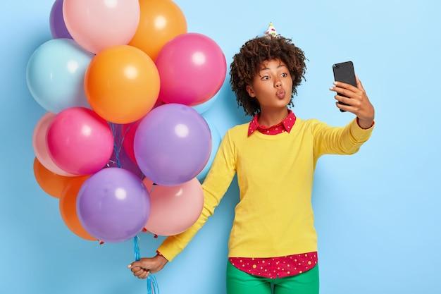 Hübsche junge frau hält bunte luftballons, während sie in einem gelben pullover posiert
