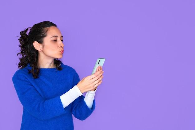 Hübsche junge frau im blauen pullover, der lokalisiert auf lila hintergrund aufwirft.