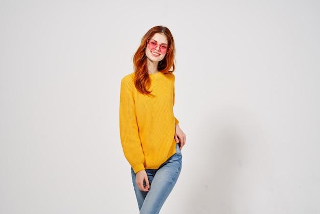 Hübsche junge frau im gelben pullover und in den rosa brillen der jeans, die aufwerfen.