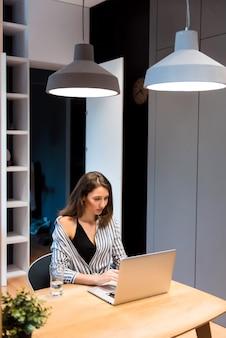 Hübsche junge frau im gestreiften hemd mit persönlichem laptop für die arbeit im business center