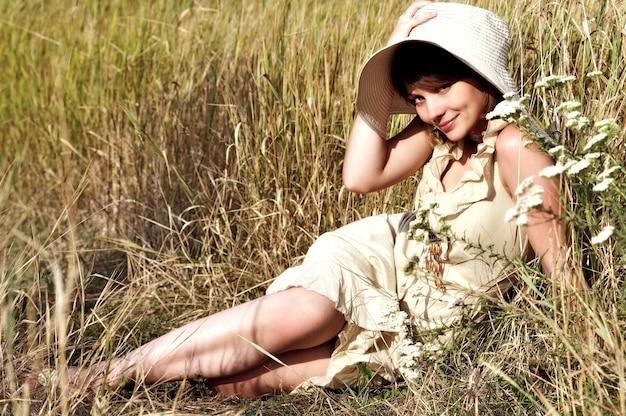 Hübsche junge frau im hellen kleid, die beige hut hält, der auf sommerfeld unter blumen liegt. frauenporträt im freien