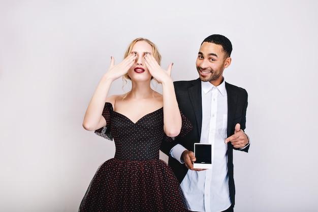 Hübsche junge frau im luxusabendkleid schließt die augen mit den händen und wartet auf die überraschung des gutaussehenden mannes mit dem ring, der hinten lächelt. valentinstag, vorschlag, liebhaber.