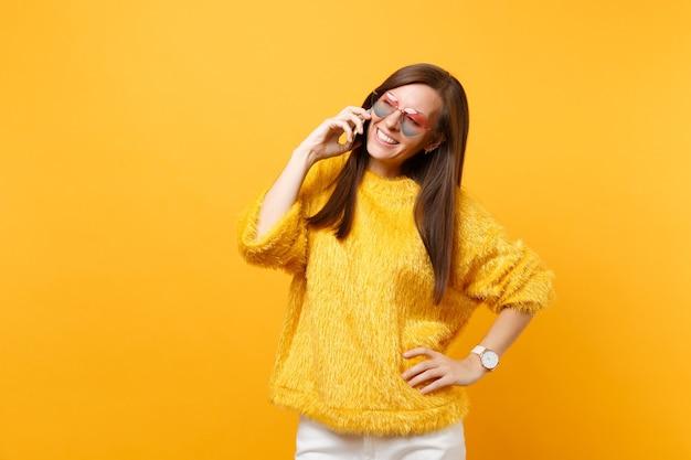 Hübsche junge frau im pelzpullover, herzbrille, die mit dem handy spricht, angenehme gespräche auf hellgelbem hintergrund führen. menschen aufrichtige emotionen, lebensstil. werbefläche.