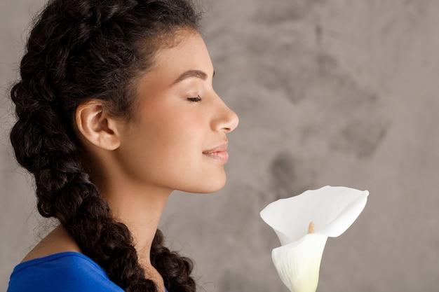 Hübsche junge frau im profil lächelnd, weiße blume haltend