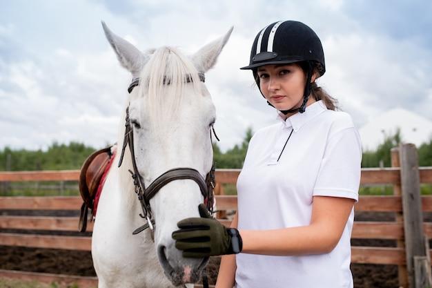 Hübsche junge frau im reithelm und in den handschuhen, die nase des weißen rennpferdes berühren, während sie heraus chiiling