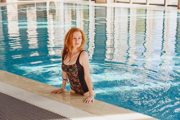 Hübsche junge frau im roten badeanzug im schwimmbad.