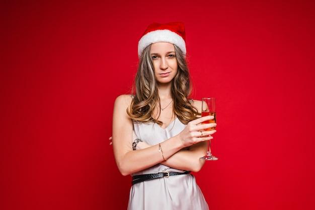 Hübsche junge frau im weihnachtsmannhut und im festlichen kleid, das das champagnerglas auf rotem hintergrund aufwirft, kopieren raum
