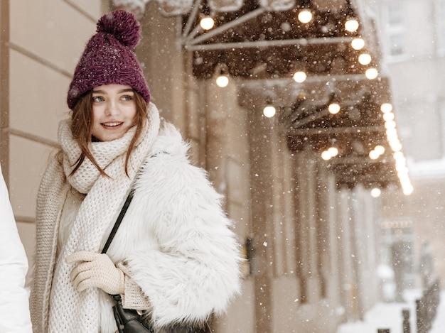 Hübsche junge frau im winteroutfit, die während des schneefalls geht