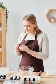 Hübsche junge frau in arbeitskleidung, die kleine flasche mit farbe öffnet, um sie in glaswaren während der seifenherstellung hinzuzufügen