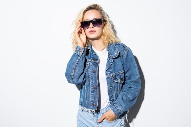 Hübsche junge frau in der sonnenbrille, gekleidet in den kurzen jeans der hipster-art, die auf weißer wandwand aufwirft