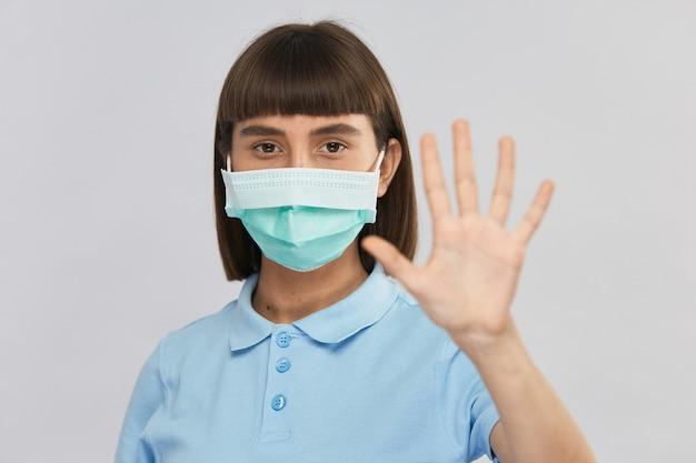 Hübsche junge frau in der sterilen entsorgungsschutzmaske auf gesicht, das zeigt, abstand mit ihrem arm zu halten Premium Fotos