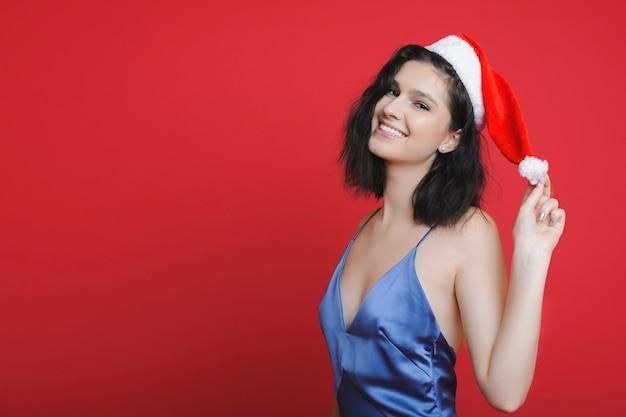 Hübsche junge frau in der weihnachtsmütze, die lächelt und kamera betrachtet, während auf hellrotem hintergrund steht