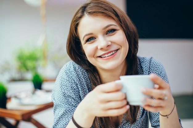 Hübsche junge frau in einem café mit einer tasse kaffee.
