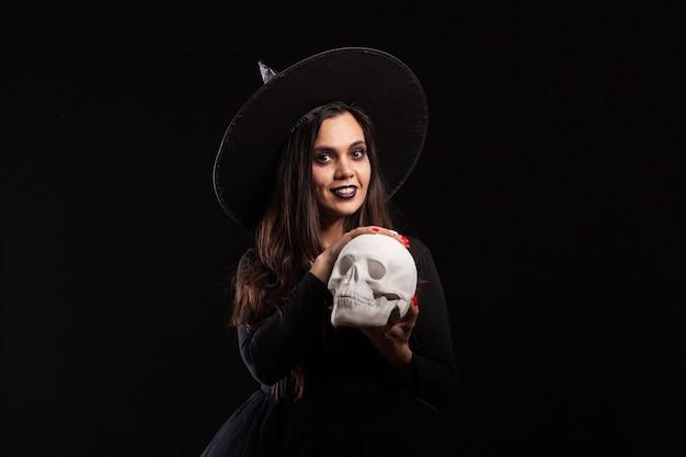 Hübsche junge frau in einem hexenkostüm für halloween-party, die böse hexerei tut. porträt der frau, die magie auf einem menschlichen schädel tut.