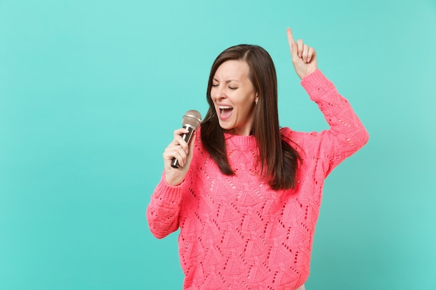 Hübsche junge frau in gestricktem rosa pullover tanzt, zeigt mit dem zeigefinger nach oben, singt lied im mikrofon einzeln auf blauem wandhintergrund, studioporträt. menschen lifestyle-konzept. kopieren sie platz.