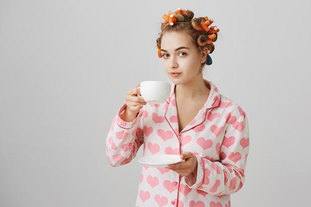 Hübsche junge frau in lockenwicklern und pyjamas, die morgenkaffee trinken