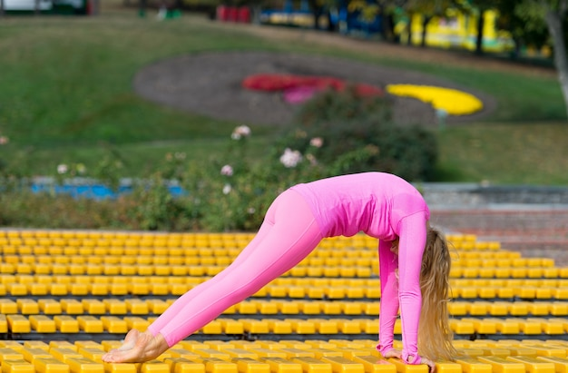 Hübsche junge frau in rosa sportkleidung, die am sonnigen tag auf gelbem hintergrund yoga-asanas im park macht