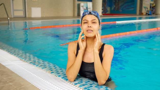 Hübsche junge frau in schwarzer mütze und anzug steht am schwimmbadrand