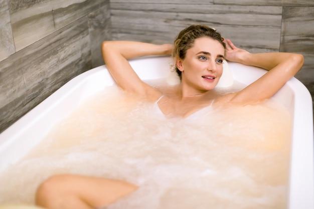 Hübsche junge frau liegt im badezimmer und schaut seitlich hände hinter ihren kopf, während sie hydromassagetherapie im spa erhält