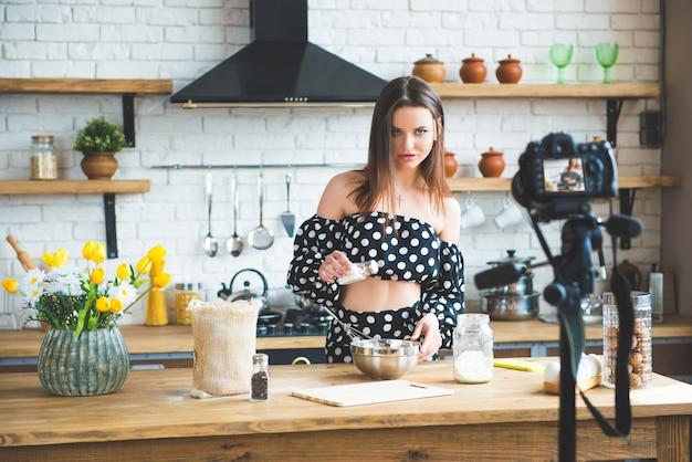 Hübsche junge frau mädchen food blogger in tupfenkleid arbeiten an einem neuen video und erklären, wie man ein gericht kocht.