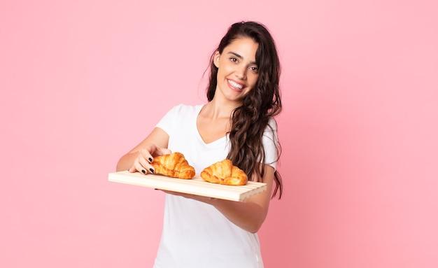 Hübsche junge frau mit einem croissant-tablett