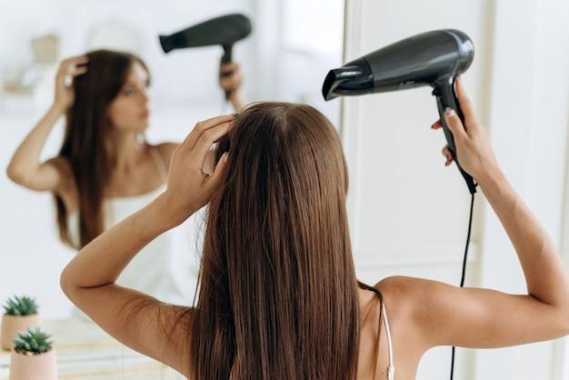 Hübsche junge frau mit einem haartrockner, die vor dem spiegel sitzt und ihr spiegelbild beim trocknen der haare betrachtet. pflege für chevelure-konzept