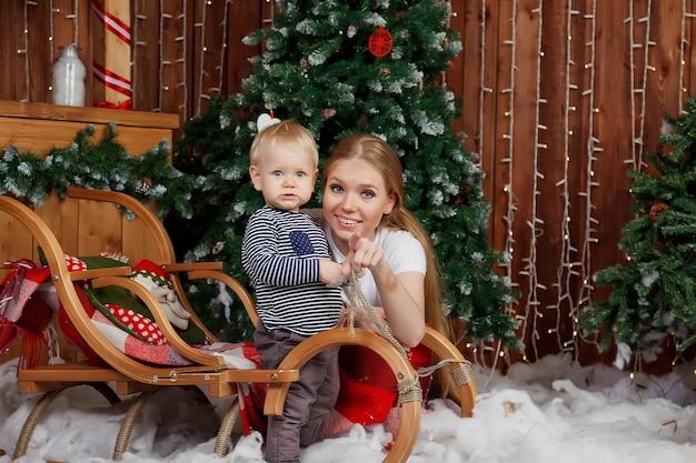 Hübsche junge frau mit einjährigem kind, das von baum des guten rutsch ins neue jahr spielt. mutter mit süßem sohn im dekorierten raum der frohen weihnachten. sie lächeln und sind glücklich