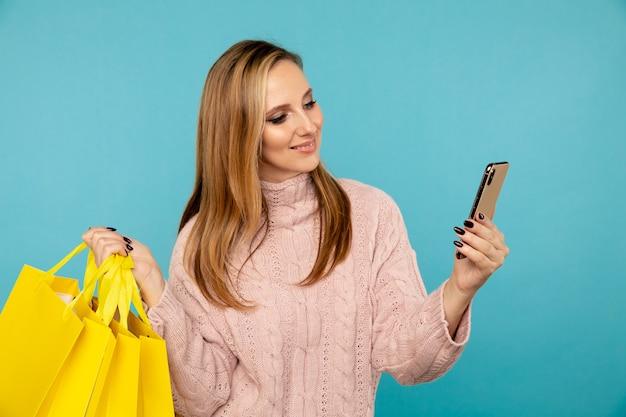 Hübsche junge frau mit gelben taschen und telefon lokalisiert auf dem blauen hintergrund. verkaufskonzept.