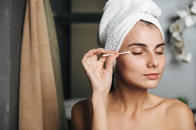Hübsche junge frau mit handtuch auf kopf, das make-up mit einem wattestäbchen vor dem spiegel im badezimmer entfernt