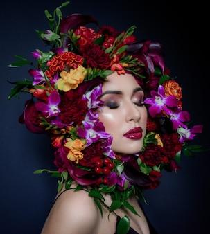 Hübsche junge frau mit hellem make-up mit geschlossenen augen, umgeben von buntem kranz aus frischen blumen auf dem dunkelblauen hintergrund