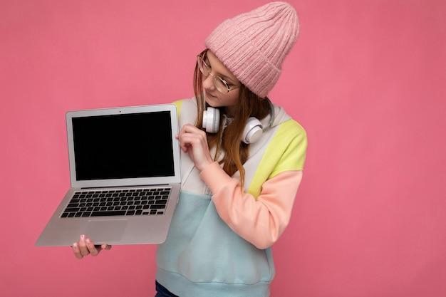 Hübsche junge frau mit hut, bunten pullover und brille, die computer-laptop mit leerer kopie hält