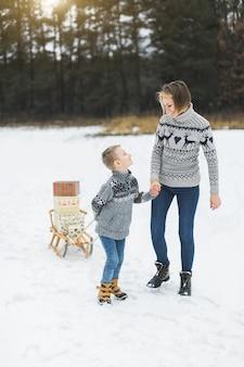 Hübsche junge frau mit ihrem sohn jungen rollt holzschlitten mit geschenkboxen verziert