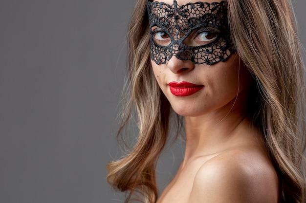 Hübsche junge frau mit karnevalsmaske