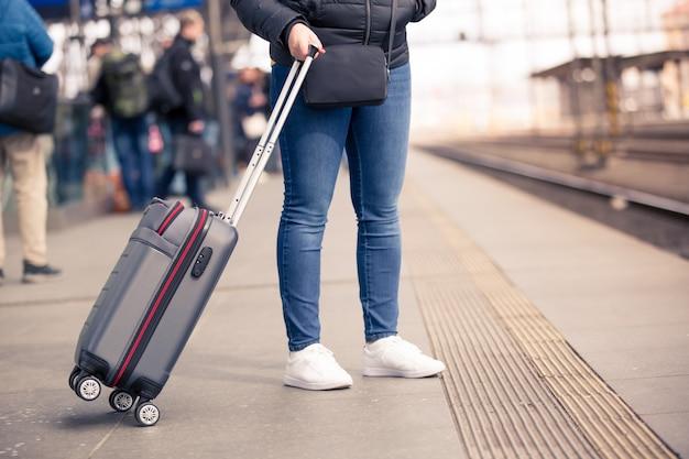 Hübsche junge frau mit kleinem handgepäck, das an der zugstation auf ihren zug, transportkonzept wartet