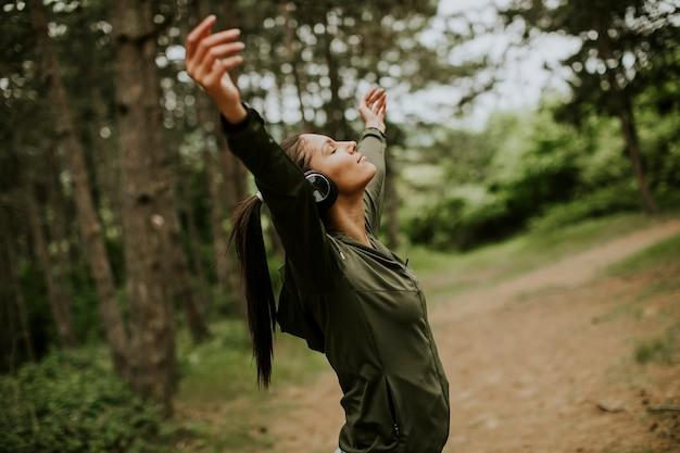 Hübsche junge frau mit kopfhörern, die ihre arme im wald ausbreiten, weil sie gerne draußen trainiert