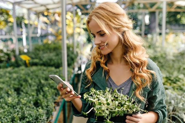 Hübsche junge frau mit lächeln liest nachricht im telefon. porträt des mädchens, das im botanischen garten im grünen baumwolloberteil geht.
