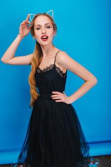 Hübsche junge frau mit langen blonden haaren auf party, posierend. tragen eines schönen schwarzen kleides, diadem mit katzenohren in diamanten auf dem kopf.