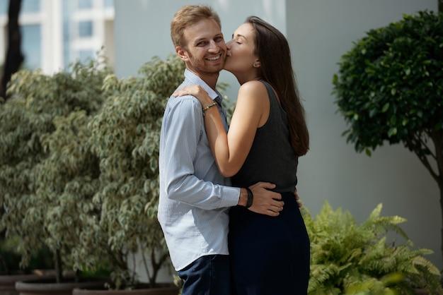 Hübsche junge frau mit langen haaren, die ihren glücklichen freund auf die wange küsst