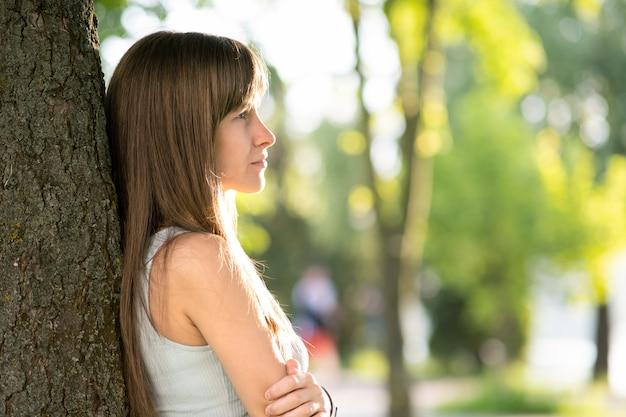 Hübsche junge frau mit langen haaren, die ordentlichen baumstamm im sommer stehen.
