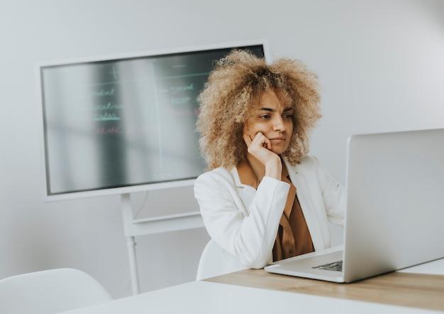 Hübsche junge frau mit lockigem haar, die im hellen büro mit großem bildschirm hinter ihr am laptop arbeitet