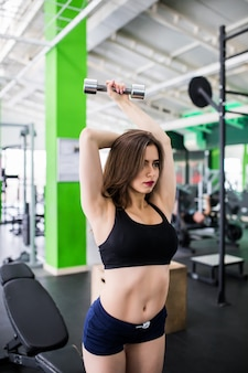 Hübsche junge frau mit metallischen hanteln macht ihr tägliches training im sportclub