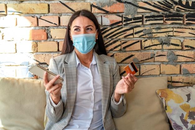 Hübsche junge frau mit schützender gesichtsmaske, die handy und kreditkarte im café verwendet