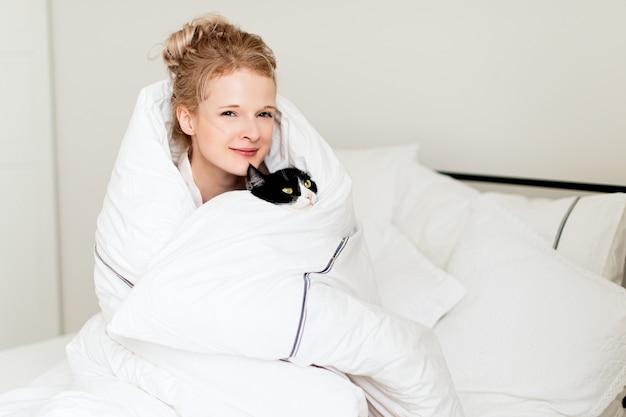Hübsche junge frau mit schwarzer katze in der decke im weißen schlafzimmer