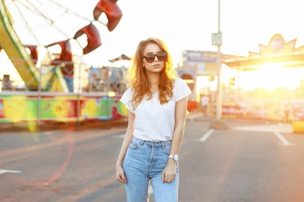 Hübsche junge frau mit sonnenbrille in einem weißen hemd und vintage jeans
