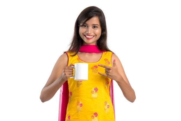 Hübsche junge frau mit tasse tee oder kaffee posiert