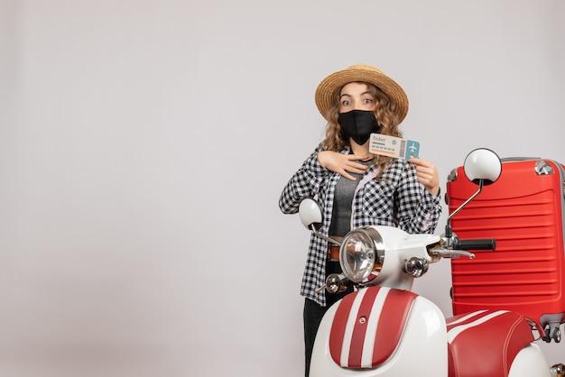 Hübsche junge frau mit ticket in der nähe des roten koffers des mopeds