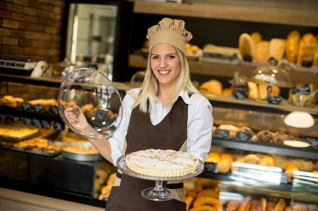 Hübsche junge frau mit torte in der bäckerei